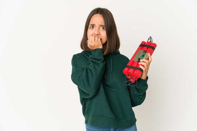 Молодая латиноамериканская женщина, держащая динамит, кусая ногти, нервничает и очень тревожится. Premium Фотографии