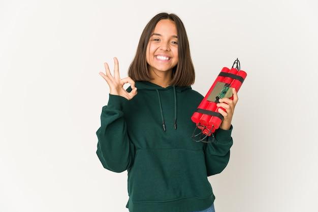 Молодая латиноамериканская женщина, держащая динамит, веселая и уверенная, показывая одобренный жест.