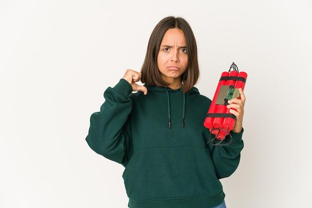 다이너마이트를 들고있는 젊은 히스패닉 여성은 자랑스럽고 자신감을 느낍니다.