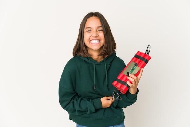 Молодая латиноамериканская женщина, держащая динамит, смеется и веселится.