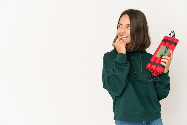 Молодая латиноамериканская женщина, держащая динамит, расслабилась, думая о чем-то, глядя на копию пространства.