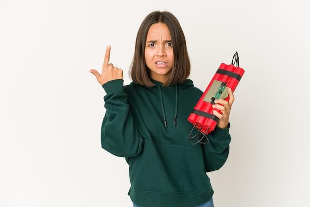 Молодая латиноамериканская женщина, держащая динамит, показывает жест разочарования указательным пальцем.
