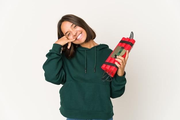 Молодая латиноамериканская женщина, держащая динамит, показывает жест мобильного телефона пальцами