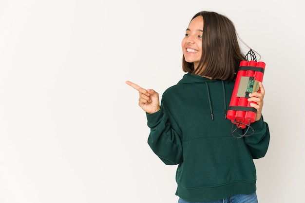 Young hispanic woman holding dynamite smiling and pointing aside, showing something at blank space.
