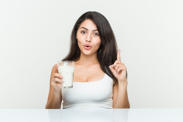 Young hispanic woman holding a glass of milk having some great idea,  of creativity.