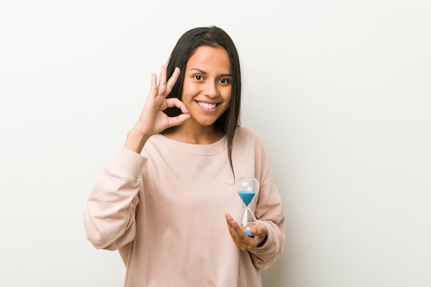 Young hispanic woman holding an hourglass cheerful and confident showing ok gesture.
