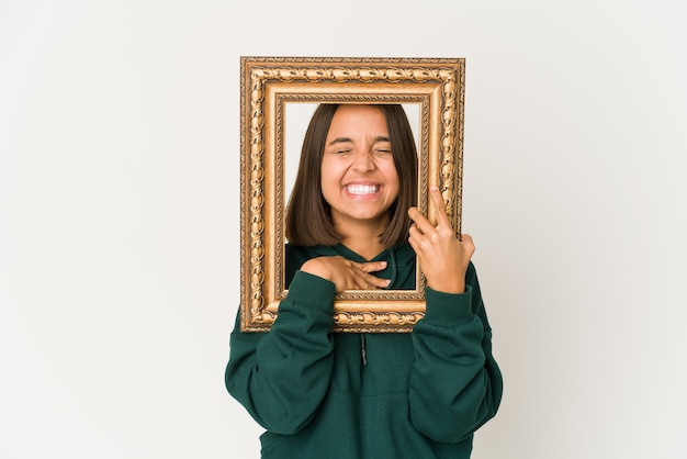 Young hispanic woman holding an old frame laughs out loudly keeping hand on chest.