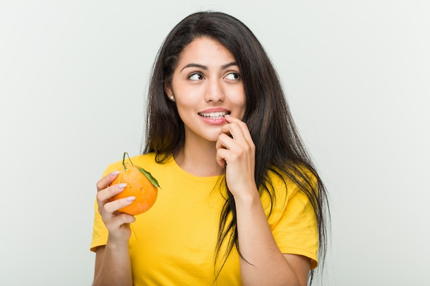 Young hispanic woman holding an orange relaxed thinking about something looking at a blank space.