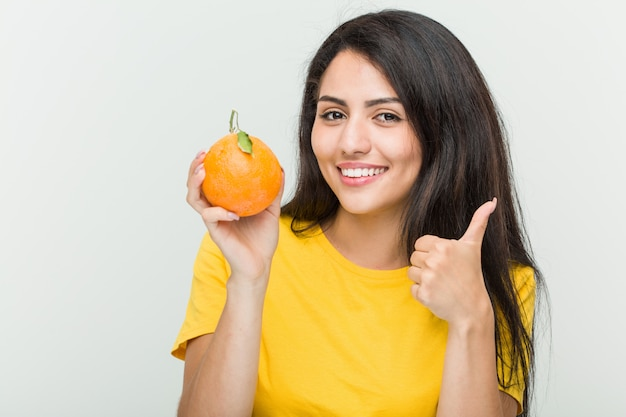 Young hispanic woman holding an orange smiling and raising thumb up