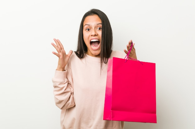 Young hispanic woman holding a shopping bag celebrating a victory or success