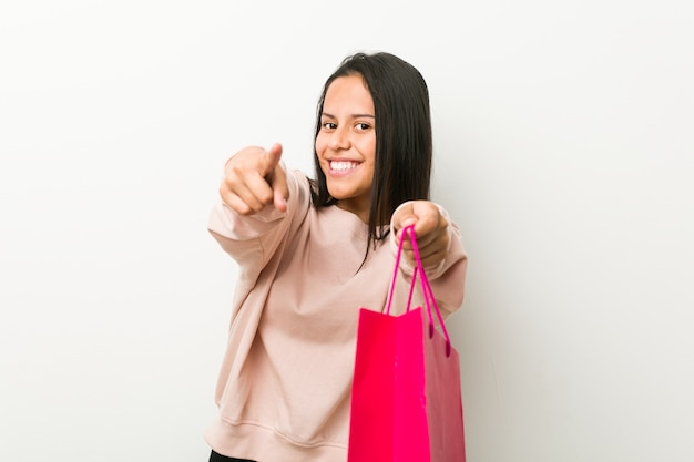 Young hispanic woman holding a shopping bag cheerful smiles pointing to front.