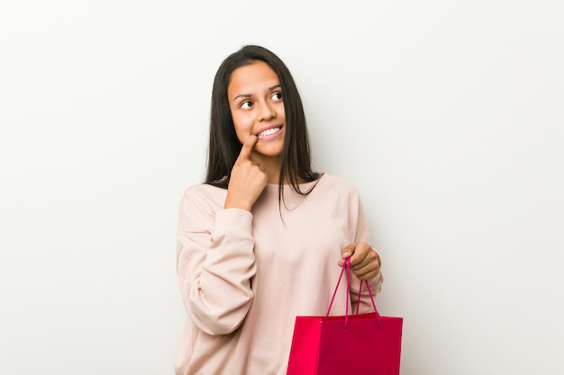 Young hispanic woman holding a shopping bag relaxed thinking about something looking at a copy space.