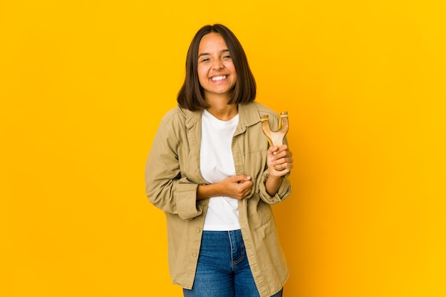Young hispanic woman holding a slingshot laughing and having fun.
