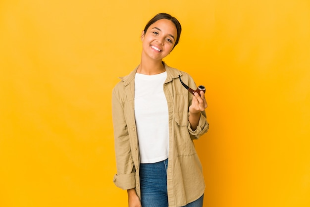 Young hispanic woman holding a smoking pipe happy, smiling and cheerful.