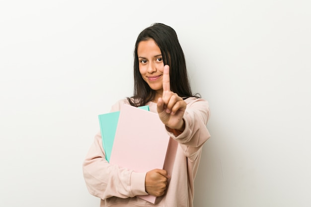 Young hispanic woman holding some notebooks showing number one with finger.