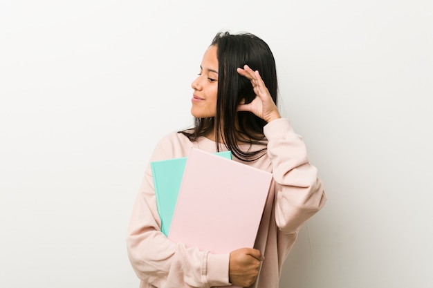 Young hispanic woman holding some notebooks trying to listening a gossip.