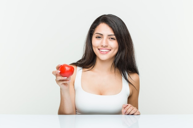 Young hispanic woman holding a tomato happy, smiling and cheerful.