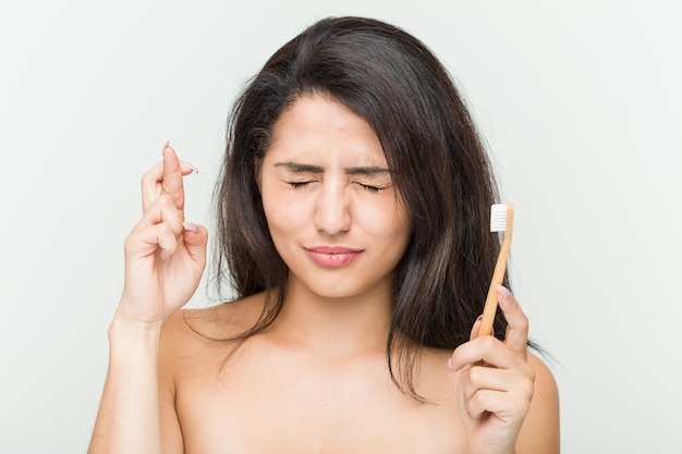 Young hispanic woman holding a toothbrush crossing fingers for having luck