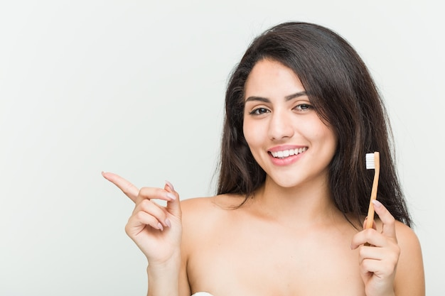 Young hispanic woman holding a toothbrush smiling cheerfully pointing with forefinger away.