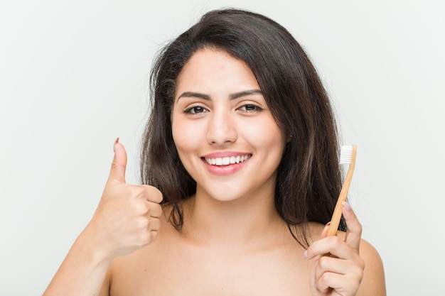 Young hispanic woman holding a toothbrush smiling and raising thumb up