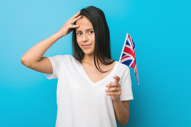 Young hispanic woman holding a united kingdom flag being shocked, she has remembered important meeting.