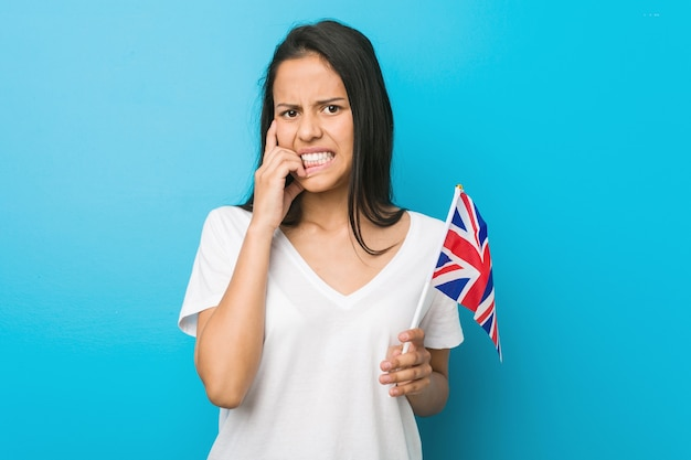 Young hispanic woman holding a united kingdom flag biting fingernails, nervous and very anxious.