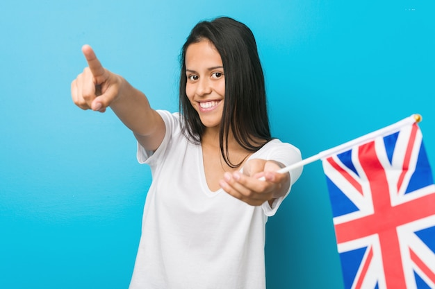 Young hispanic woman holding a united kingdom flag cheerful smiles pointing to front.