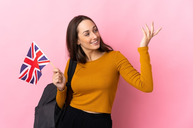 Young hispanic woman holding an united kingdom flag extending hands to the side for inviting to come