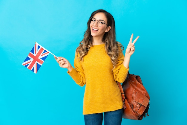 Young hispanic woman holding an united kingdom flag isolated on blue background smiling and showing victory sign