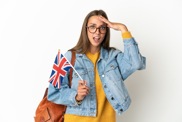 Young hispanic woman holding an united kingdom flag over isolated white background doing surprise gesture while looking to the side