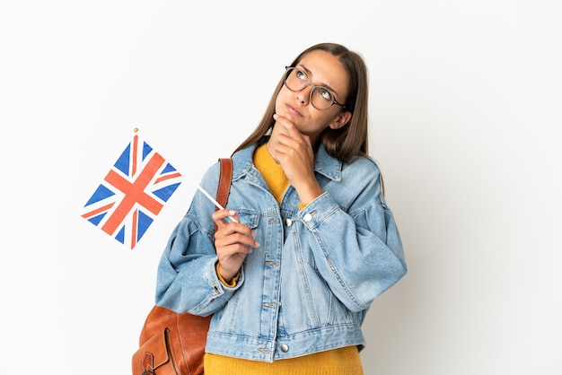 Young hispanic woman holding an united kingdom flag over isolated white background having doubts
