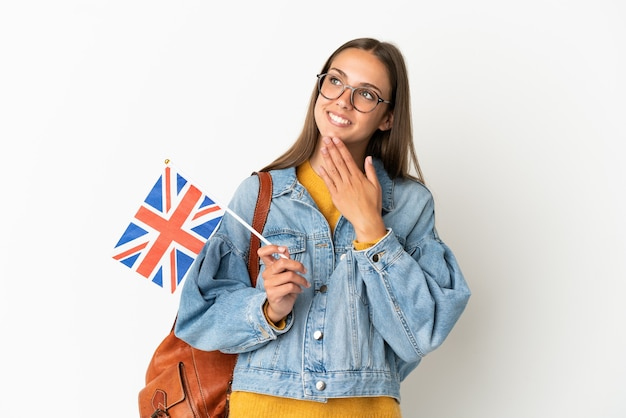 Young hispanic woman holding an united kingdom flag over isolated white background looking up while smiling