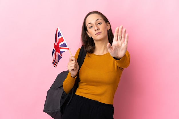 Young hispanic woman holding an united kingdom flag making stop gesture