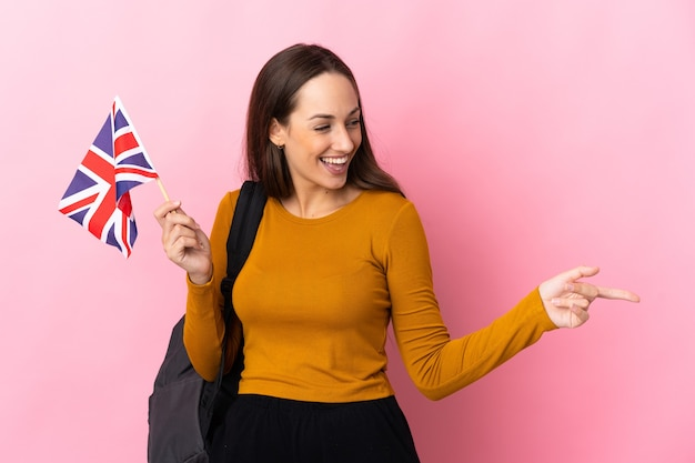 Young hispanic woman holding an united kingdom flag pointing finger to the side and presenting a product