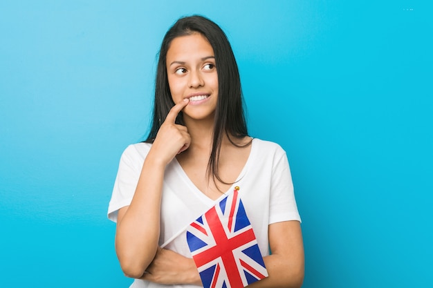 Young hispanic woman holding a united kingdom flag relaxed thinking about something