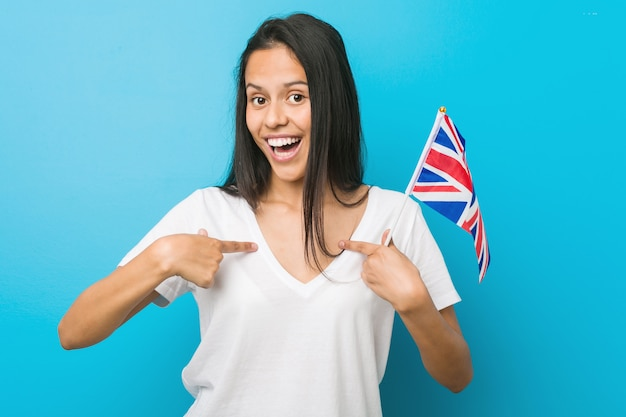 Young hispanic woman holding a united kingdom flag surprised pointing at himself, smiling broadly.