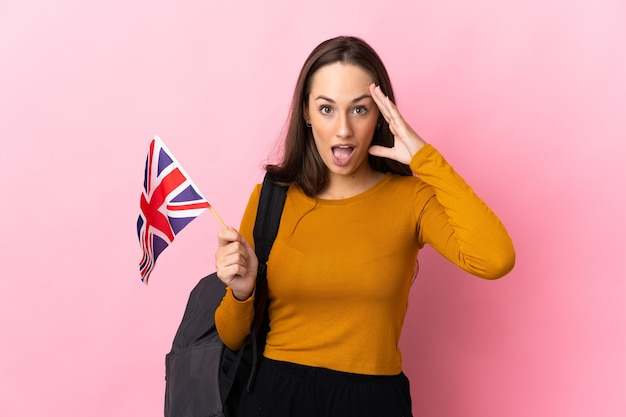 Young hispanic woman holding an united kingdom flag with surprise expression