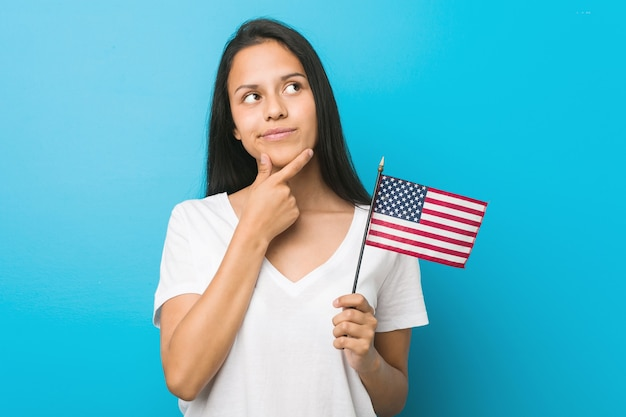 Young hispanic woman holding a united states flag looking sideways with doubtful and skeptical expression.