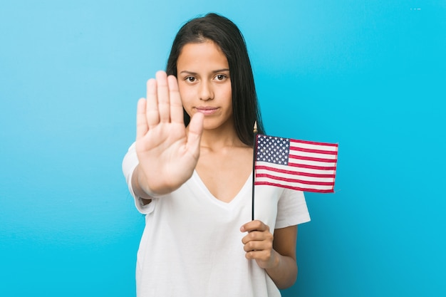 Young hispanic woman holding a united states flag standing with outstretched hand showing stop sign, preventing you.