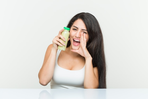 Young hispanic woman holding a vegetable drink shouting excited to front.