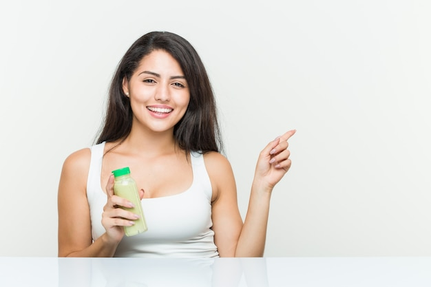 Young hispanic woman holding a vegetable drink smiling cheerfully pointing with forefinger away.