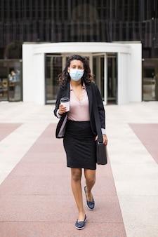 공식적인 옷과 얼굴 마스크를 쓴 젊은 히스패닉 여성이 비즈니스 건물 입구 근처를 걷고 있습니다.