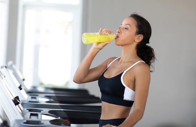 ジムのトレッドミルで走り、水を飲むスポーツウェアの若いヒスパニック系女性。健康的なライフスタイルとスポーツの概念。