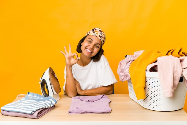 Young hispanic woman ironing clothes isolated cheerful and confident showing ok gesture.