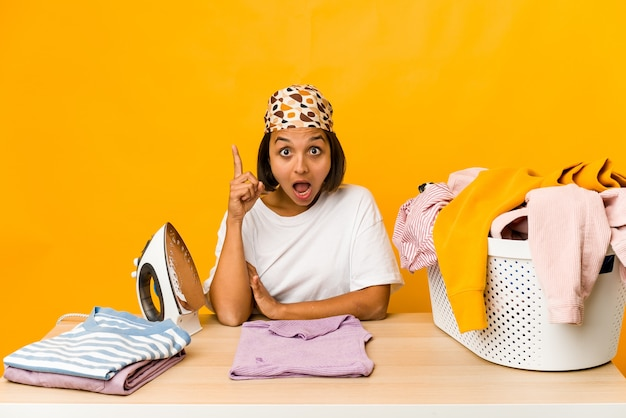 Young hispanic woman ironing clothes isolated having an idea, inspiration concept.