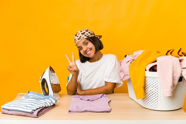 Young hispanic woman ironing clothes isolated joyful and carefree showing a peace symbol with fingers.