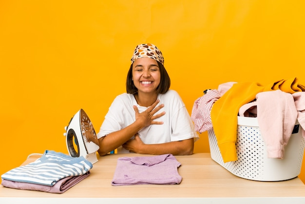 Young hispanic woman ironing clothes isolated laughs out loudly keeping hand on chest.