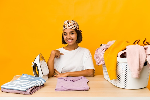 Young hispanic woman ironing clothes isolated person pointing by hand to a shirt copy space, proud and confident
