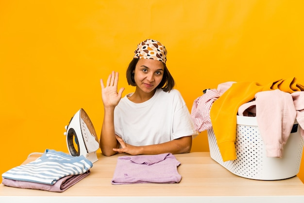Young hispanic woman ironing clothes isolated smiling cheerful showing number five with fingers.
