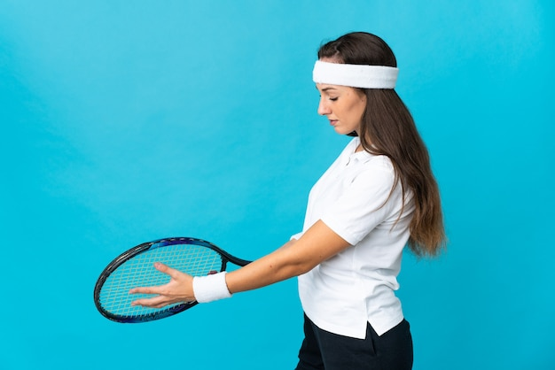 Young hispanic woman over isolated blue background playing tennis